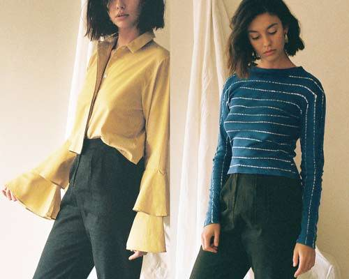 Woman wearing yellow frill sleeve blouse tucked into black high waisted trousers and woman wearing organic cotton wide and high neck long sleeve tee from sustainable fashion brand Leo Strange