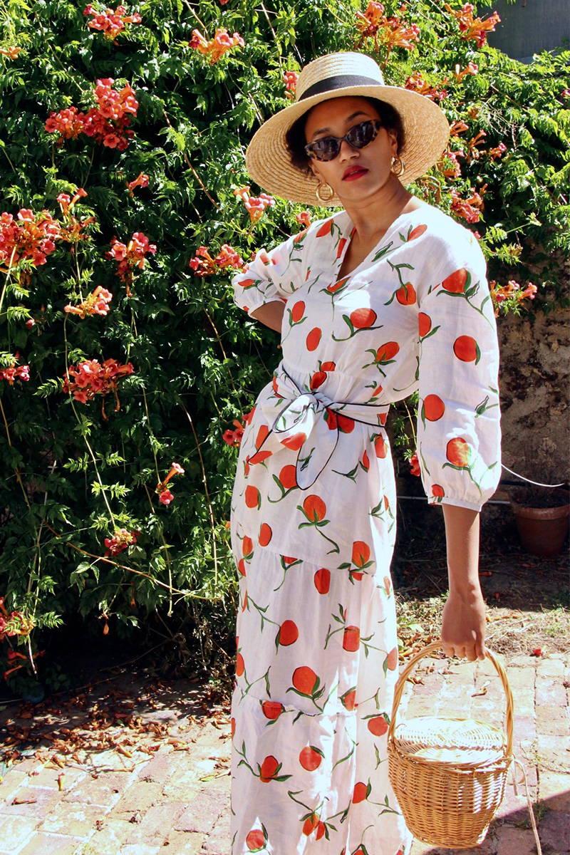 Lena Farl wearing YOLKE's Orange Babushka Dress wearing a sun hat and standing amongst flowers