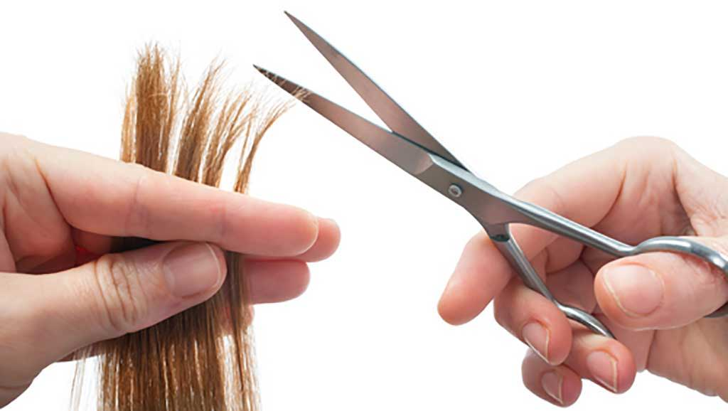 hands holding scissors about to trim split ends