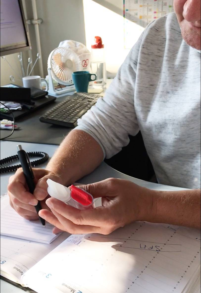 Photo of someone holding a red nomad tester and writing down the results