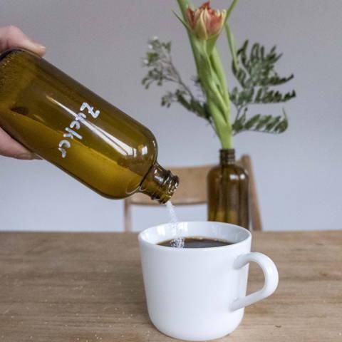 Eine Flasche Rho Kombucha wird als Zuckerbehälter benutzt und kippt etwas Zucker in einen Kaffee