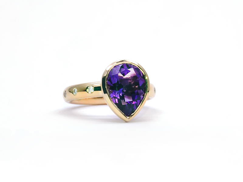 Yellow gold ring with diamond on the body and large pear cut amethyst in the center.