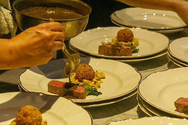 Wagyu beef, meatball, elbows pasta and salad being plated.
