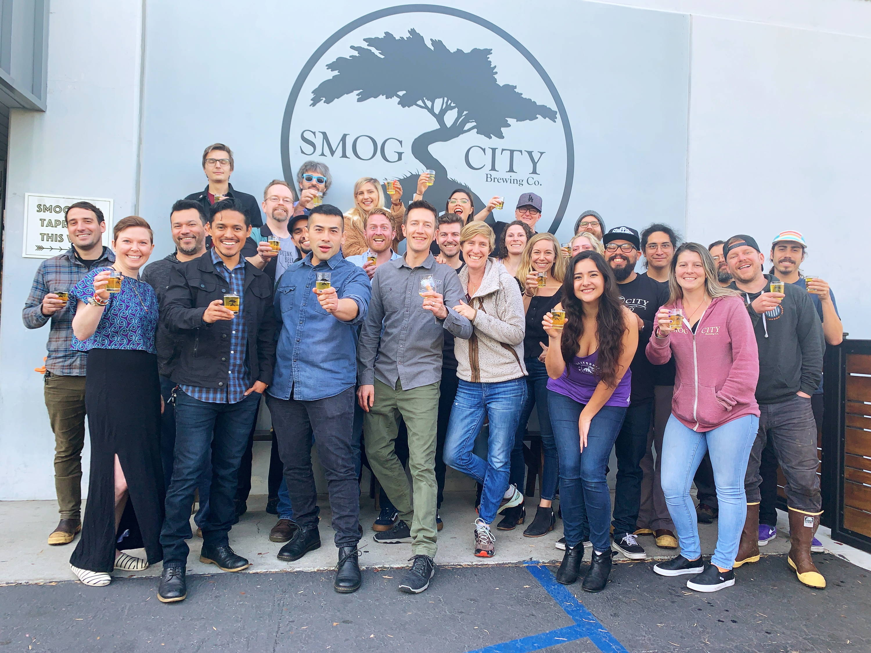 All staff photo of Smog City. Everyone is cheering, one person is laying on the floor. Many people are laughing, and loving being a part of the Smog City crew.