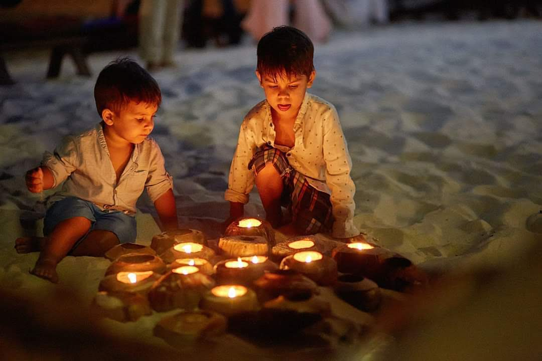 Two boys playing with candles on the beach. Children birthday party catering services in Kingston and South London.
