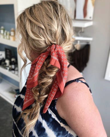 sideview of a blonde side braid with a scarf tied in it