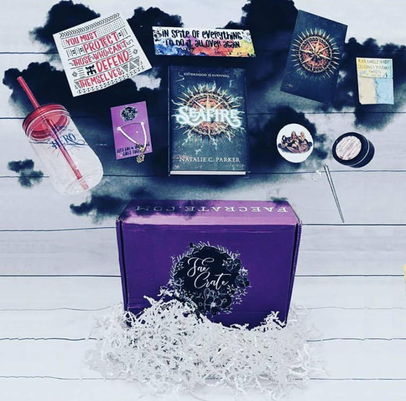 August 2018 Deadly Dames box included Warcross Bookmark, Daugher of Smoke and Bone Bracelet, Little Red Bird Candle, Yulemas Sweets Soaps, Deadly Dames Sticker and Art Print, Hermine Wand Keychain, Caraval 25oz Mason Jar, and Seafire by Natalie C. Parker.