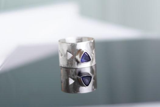 Широкое геометрическое кольцо с треугольным аметистом или перидотом.