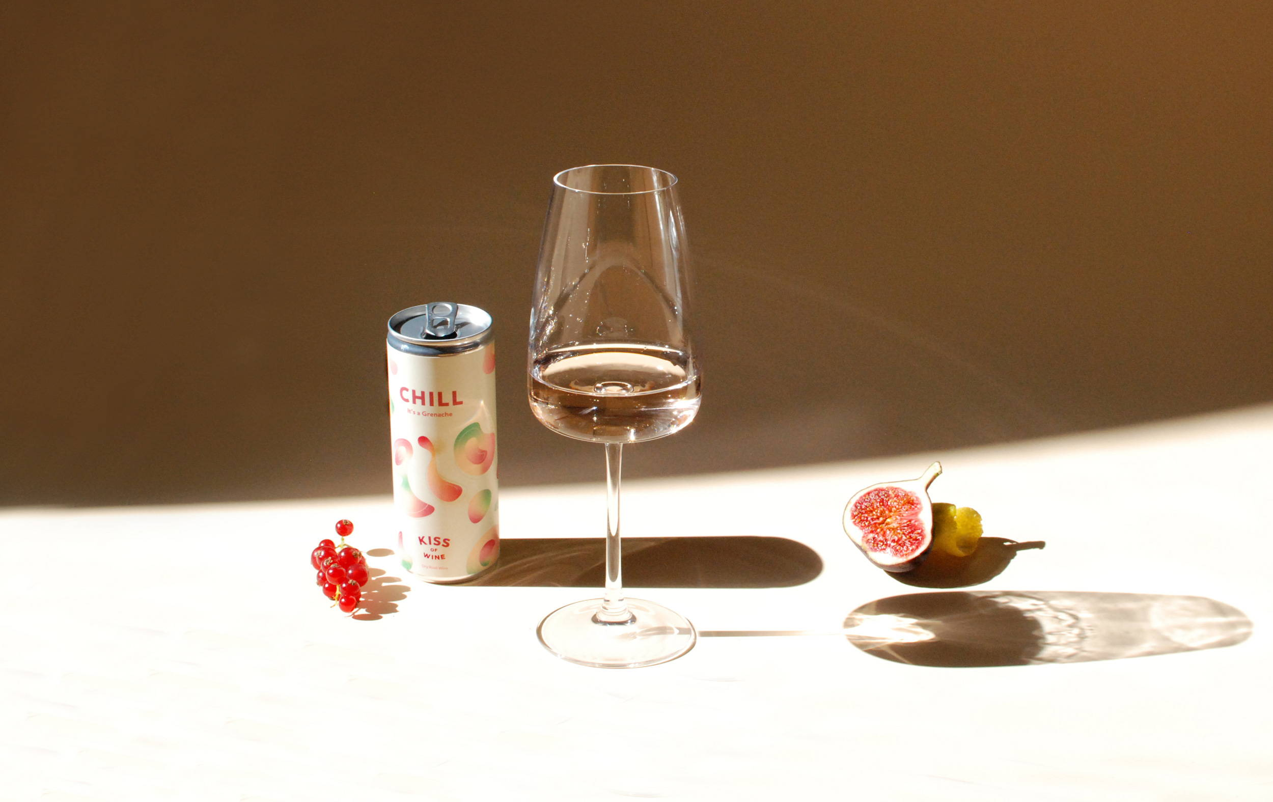 Poured glass of Chill Caladoc Rose surrounded by can, red berries and half a fig.