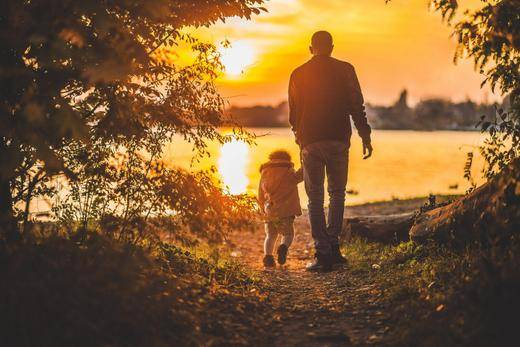 Photo of Father and child walking in the sunset