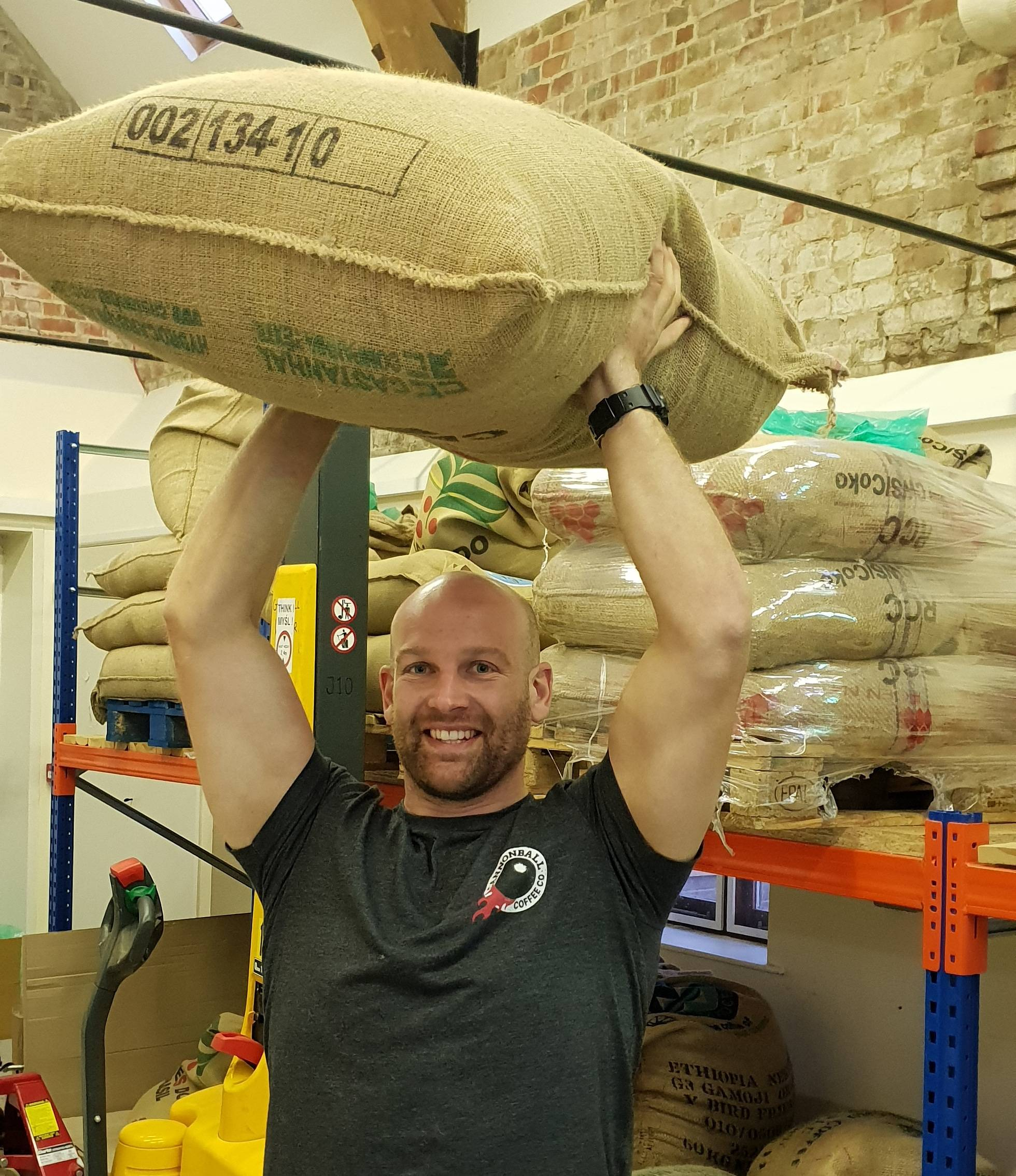 founder of cannonball coffee holding a bag of green coffee beans