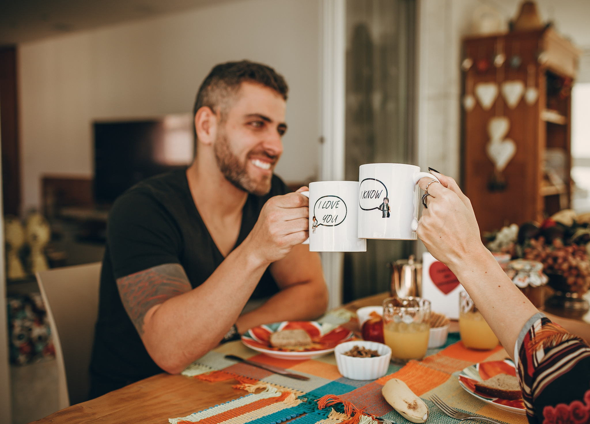 Image of an attractive man sitting with a woman out of frame having breakfast together. He is smiling and holding a white coffee mug up to the woman's coffee mug.