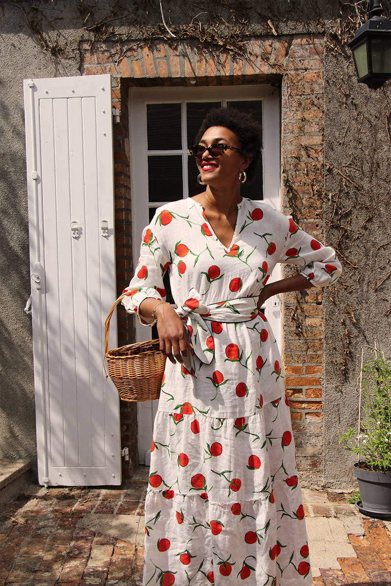 Lena Farl wears YOLKE Orange Linen Babushka Dress in front of a French cottage