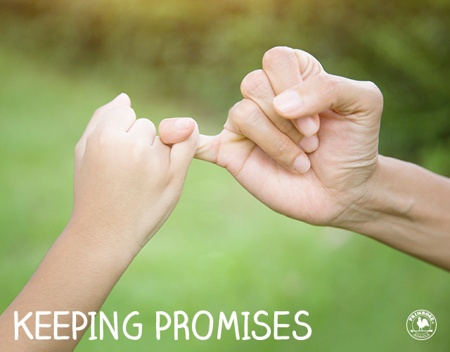 Mother and child's fingers entwined in a pinky swear