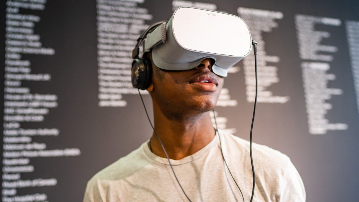 A young man wearing a virtual reality headset that covers his eyes
