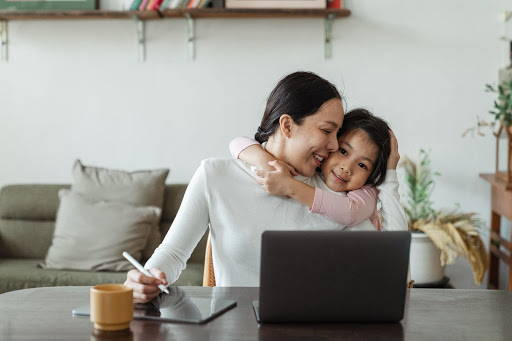Mother hugging her daughter, at the desk doing work - Photo by Ketut Subiyanto from Pexels