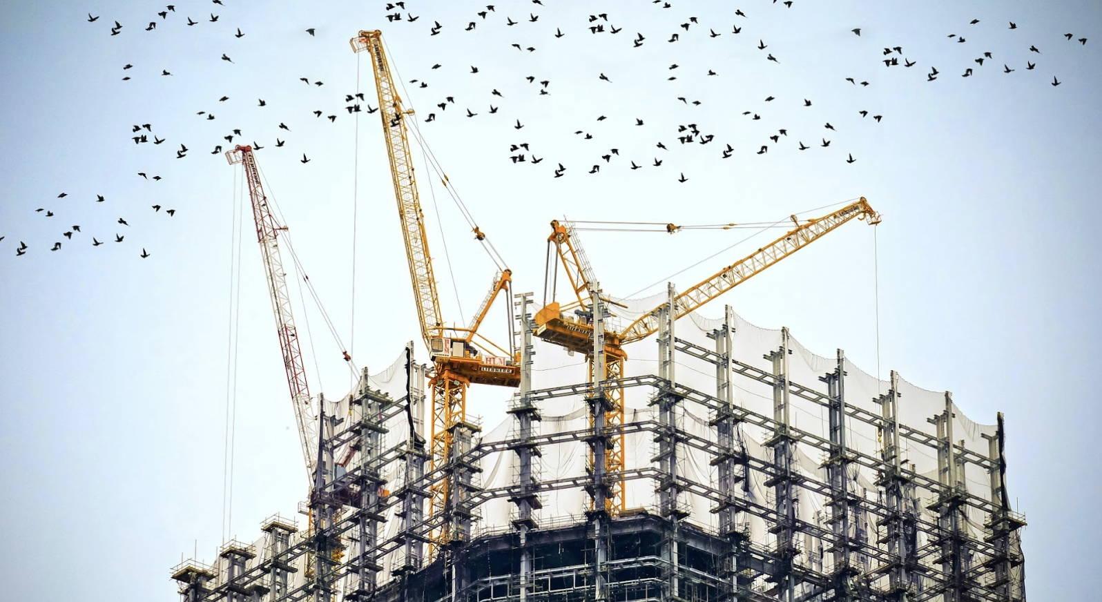 Kraner på en byggeplads, som henviser til investering i ejendom