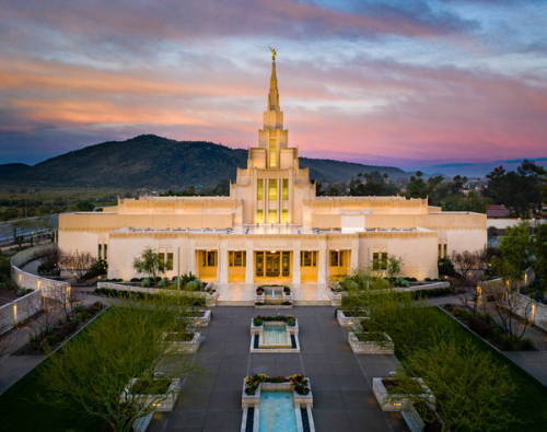 Arial photo of the Phoenix Temple glowing against the evening sky.