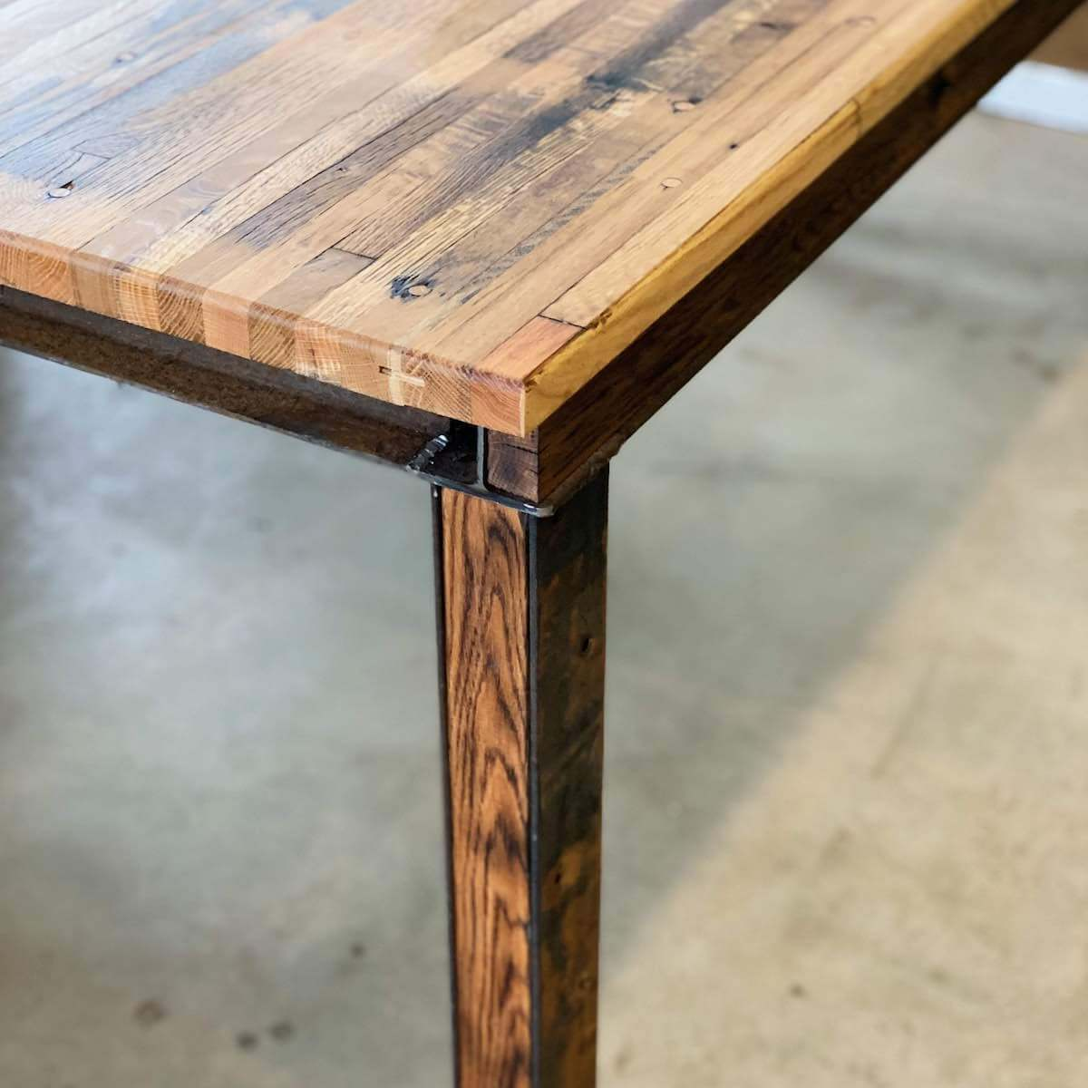 side view of inlaid wood leg on reclaimed wood table