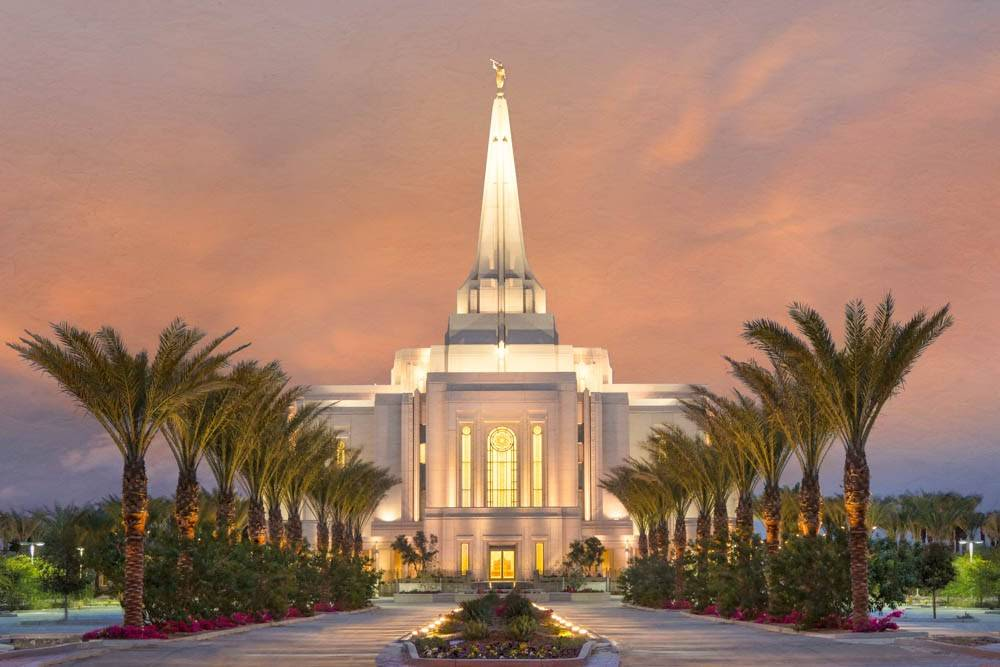 Photo of Gilbert Arizona LDS Temple. The path to the doors is lined with palm trees.