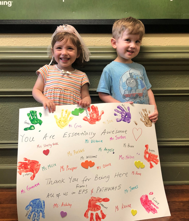 A girl and boy holding a sign thanking teachers for being there with teacher names on it