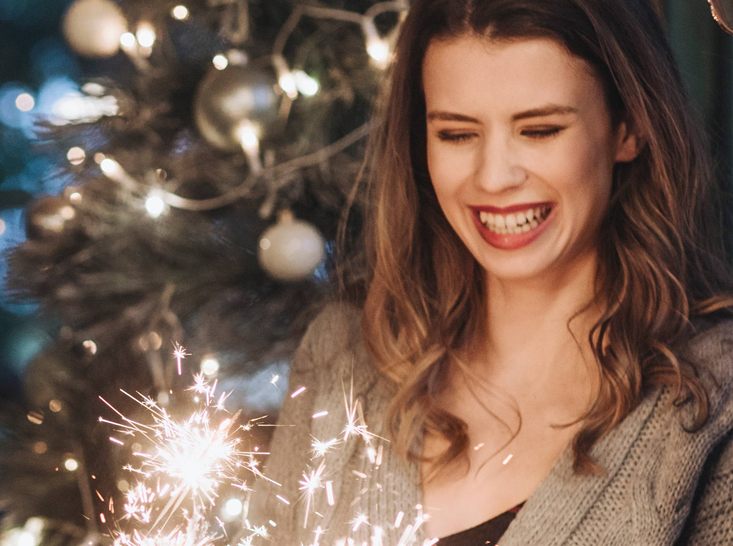 brunette women near holiday decorations and sparklers
