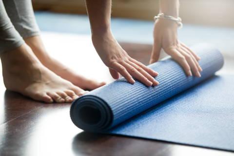 Eine Frau bereitet sich aktiv auf ihre  Yoga Stunde vor.