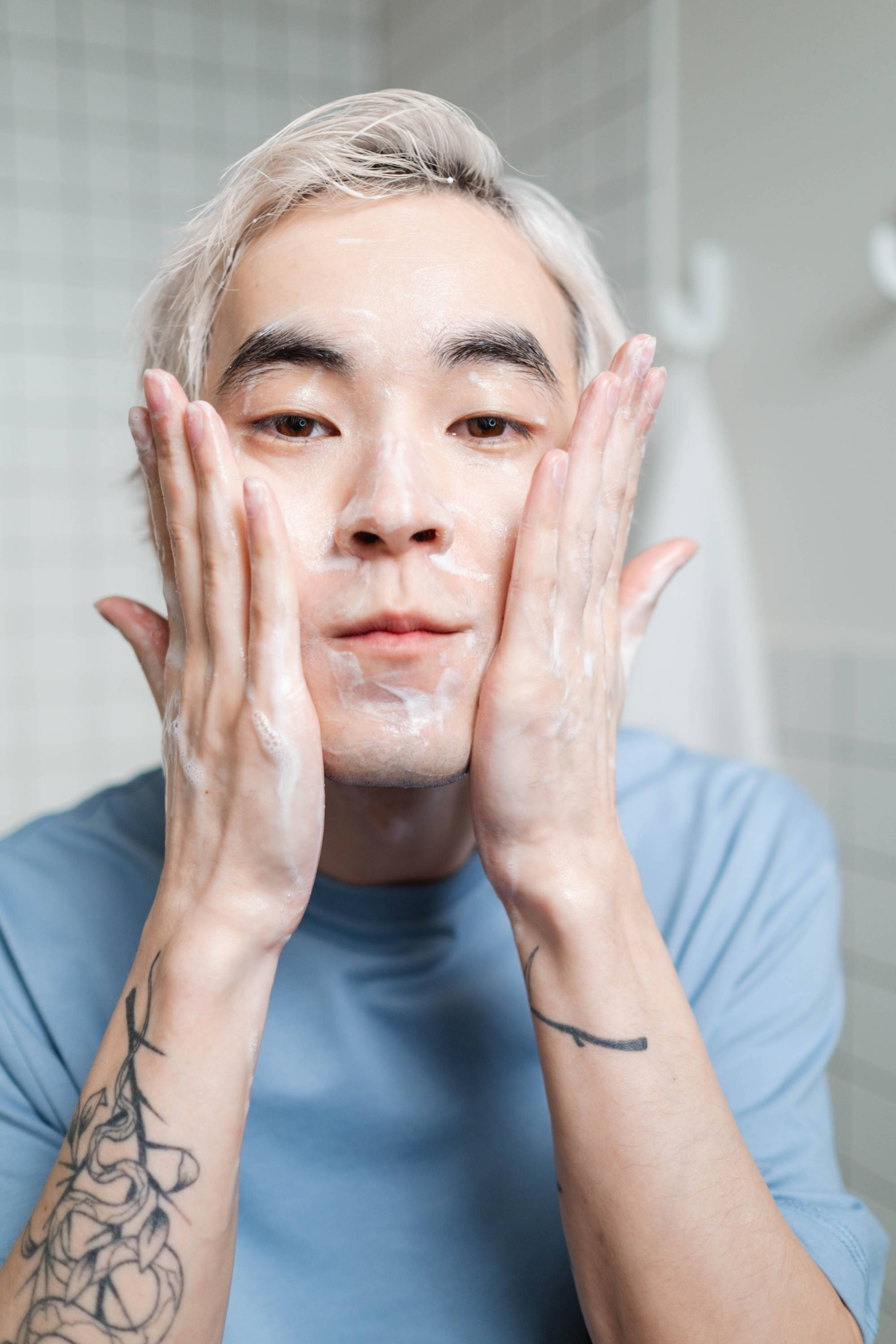 man washing his face with a cleanser