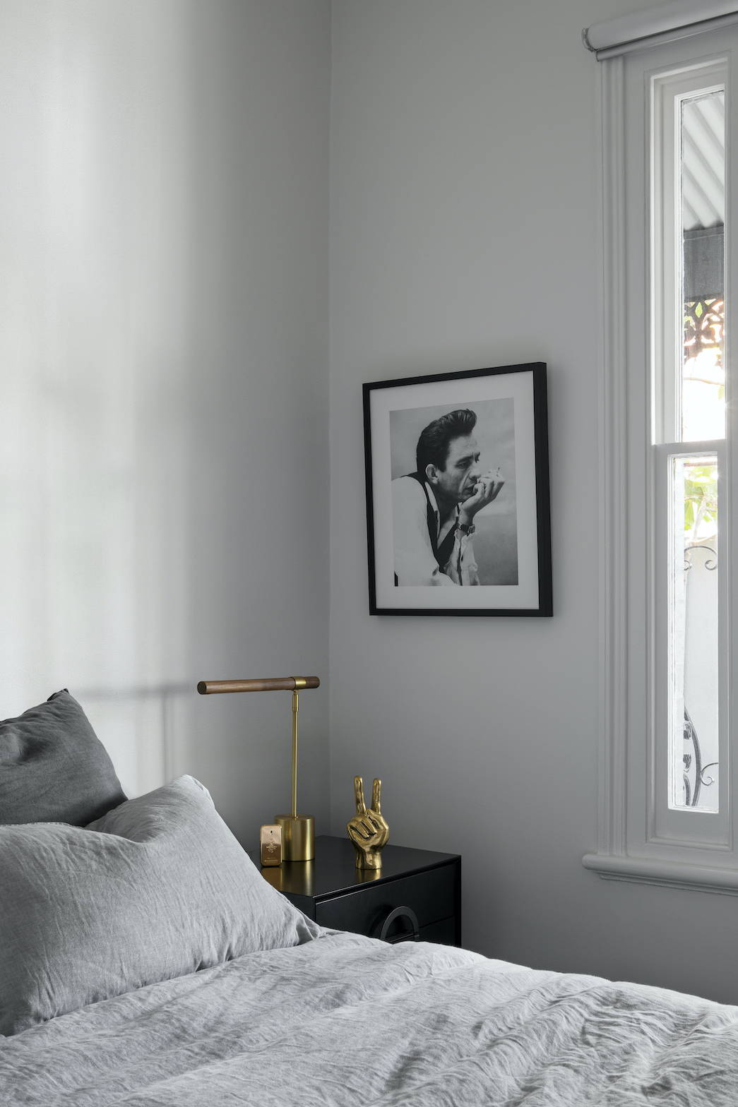 Black and white framed photograph of Johnny Cash in a bedroom setting