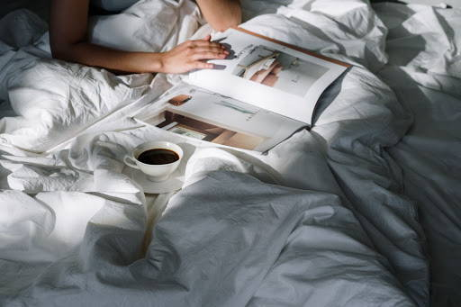 Person reading a magazine in bed with a cup of coffee beside herPhoto by cottonbro from Pexels