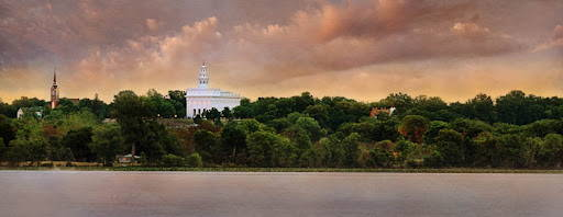 Panoramic picture of the Nauvoo Temple surrounded by green trees from across a river.