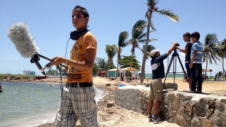 Boys learning how to use film equipment on a beach in Cuba