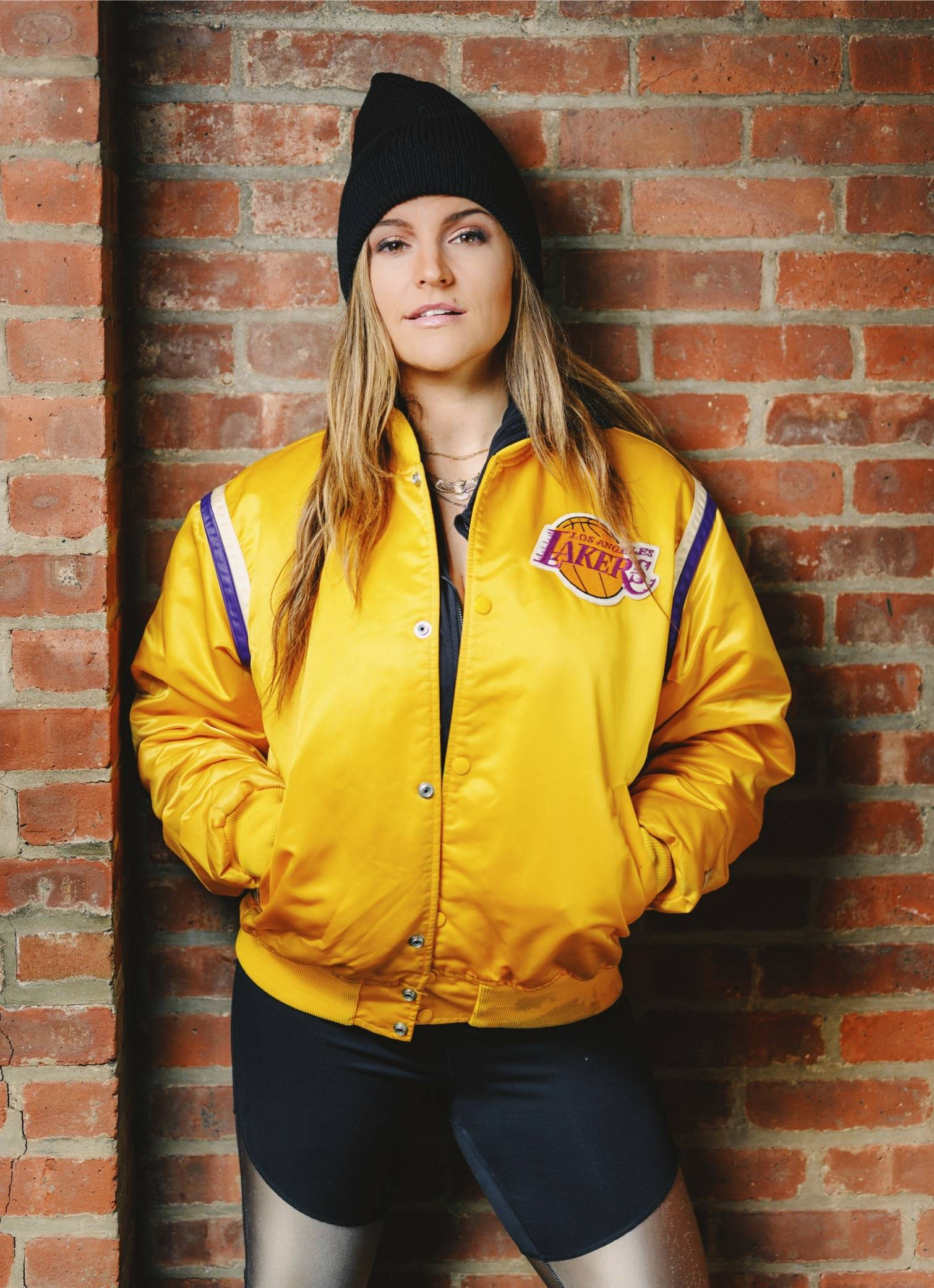 Photo of Annie O'Donnell, wearing an LA Lakers jacket, standing against a brick wall