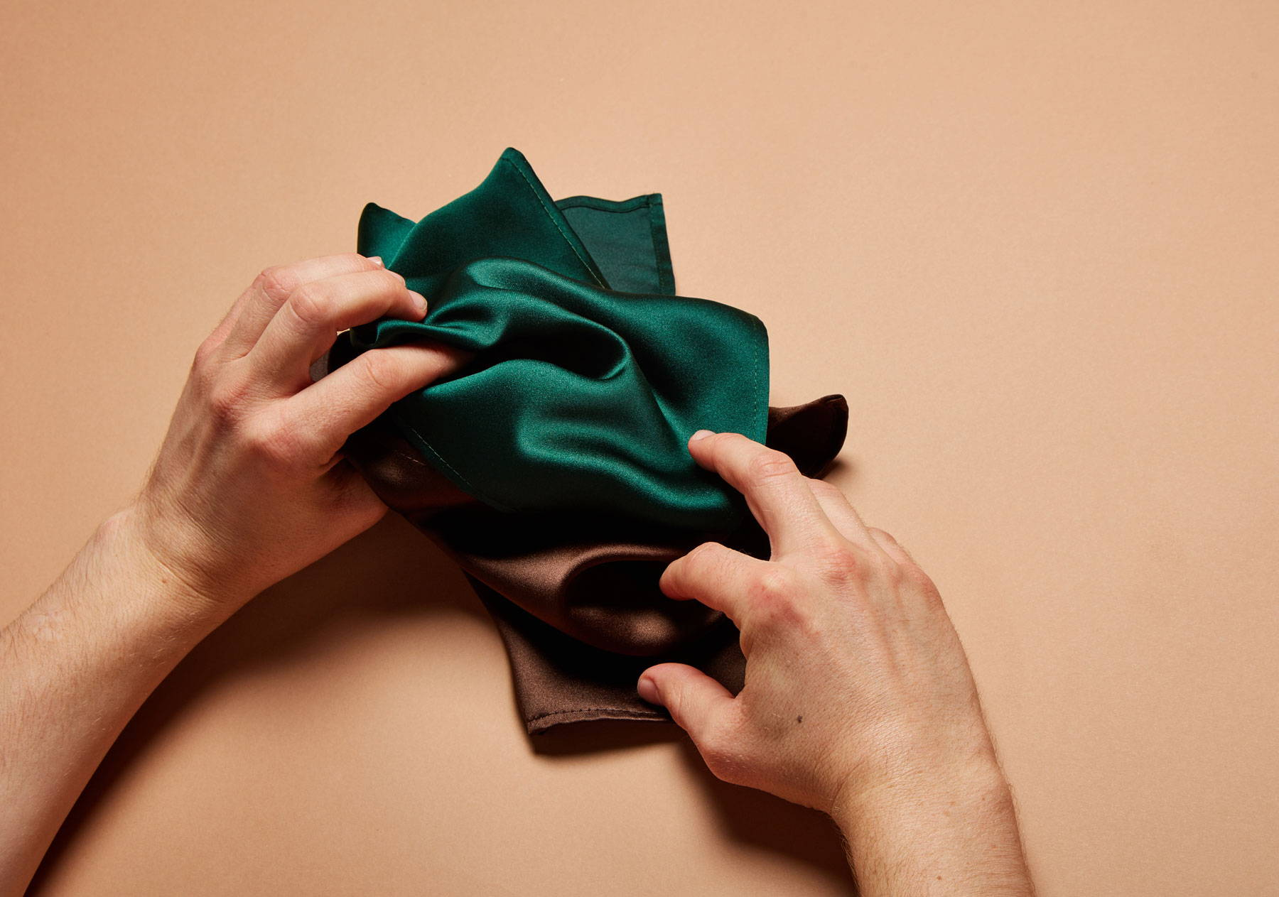 Hands holding green and brown pocket squares