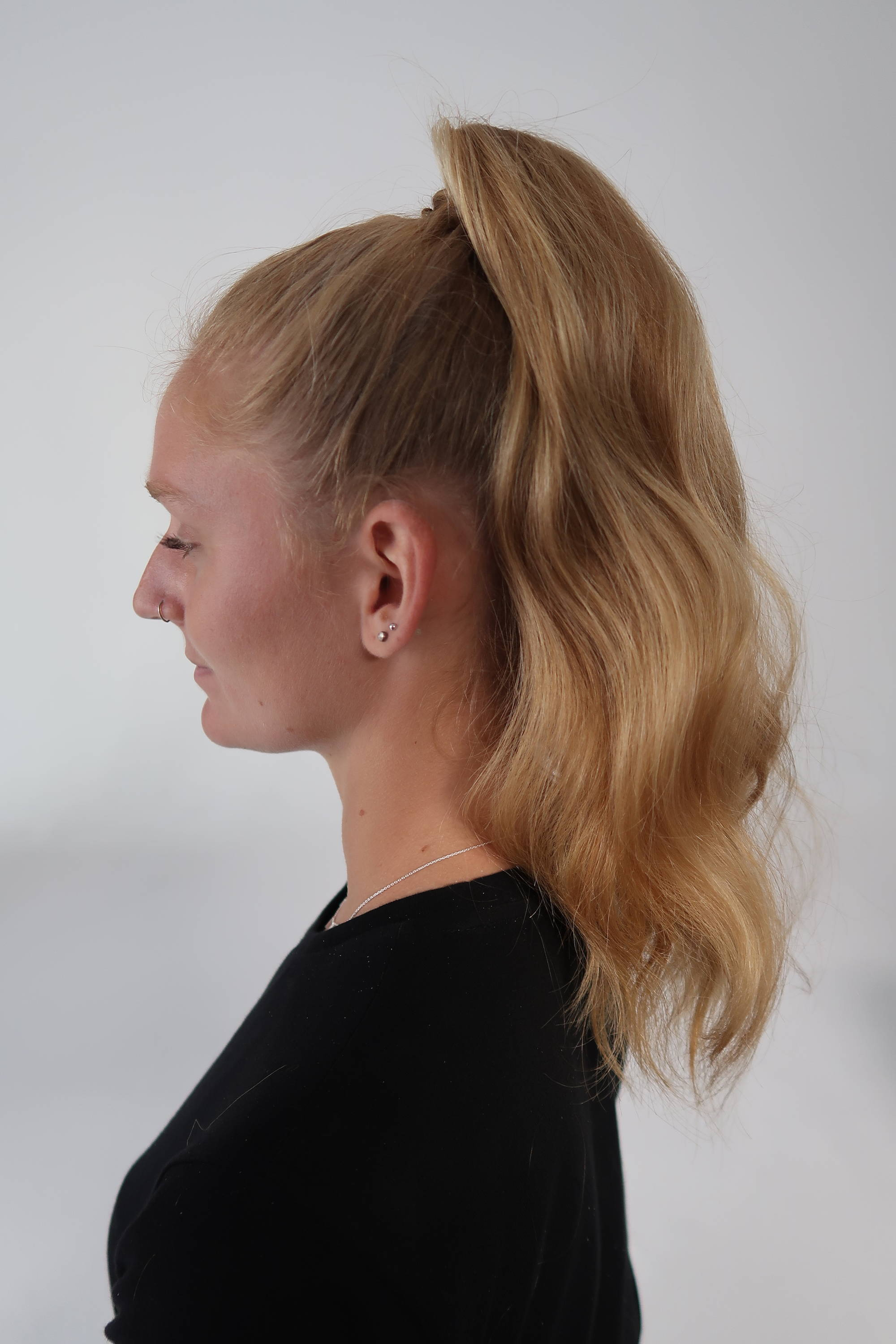 photo of the backview of a blonde woman's wavy ponytail hairstyle