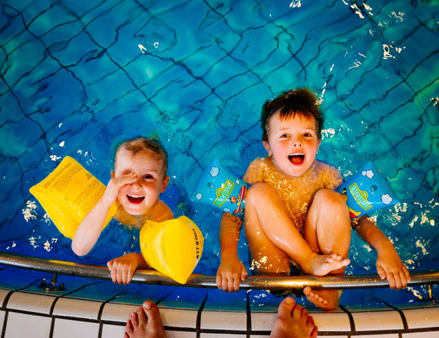 kids laughing and swimming by the pool