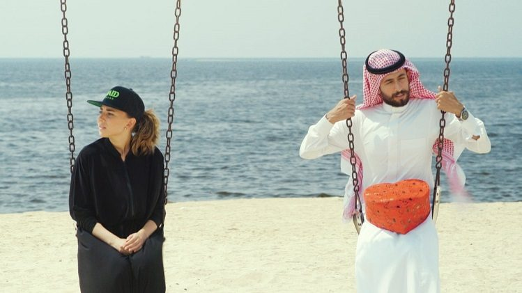 A woman in black and a man in white sit on swings on the beach.