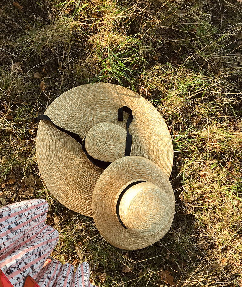 Female Narratives day wear dress shoot: Straw hats on grass