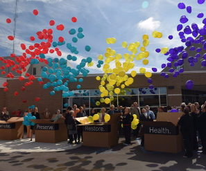Celebration in front of DeKalb Health facility with balloon release