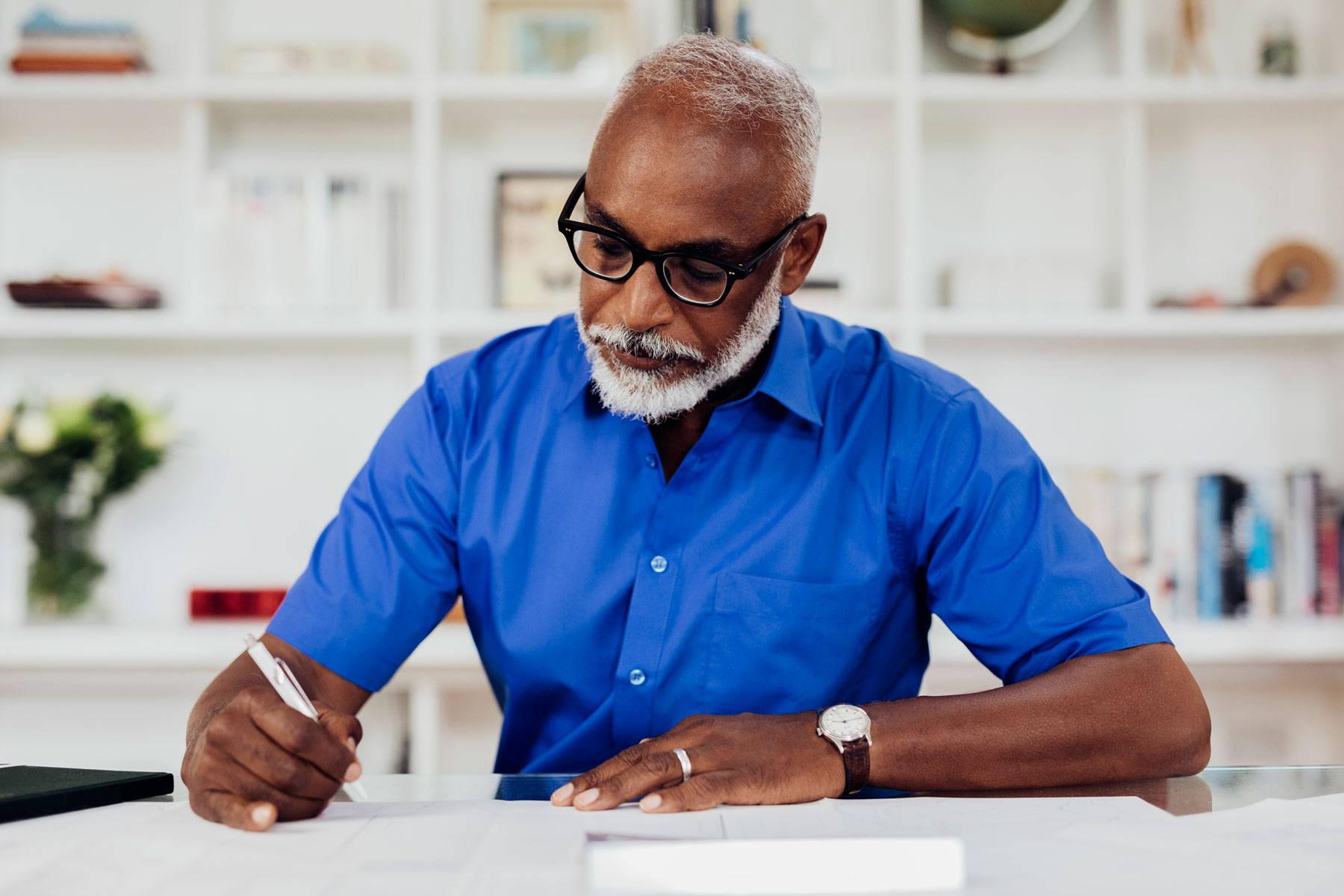 Man writing in bright blue shirt