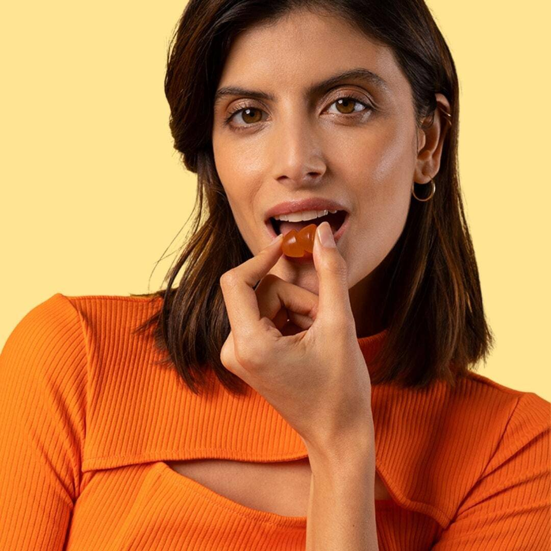 beautiful woman eating two energy gummies