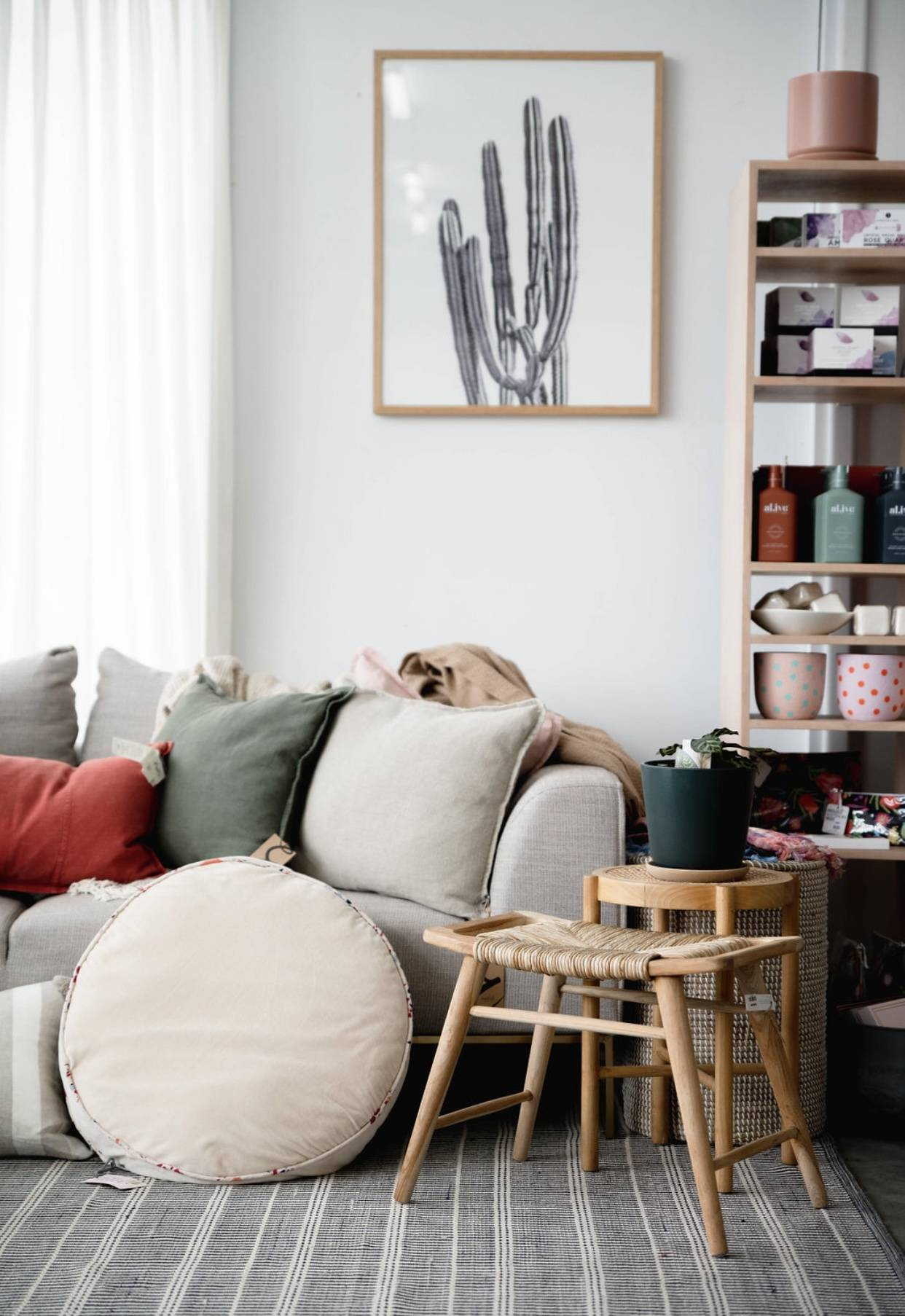 Picture of a room- grey/ beige lounge with cushions- some square, some round. All neutral tones. Walls are white with a large print of a cactus. This is a room in Style Leaf Co located in Katanning.