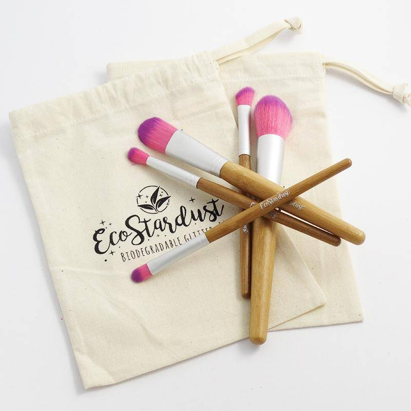 Picture shows multiple vegan bamboo makeup brushes arranged in a star shape, sitting on a cloth carry bag