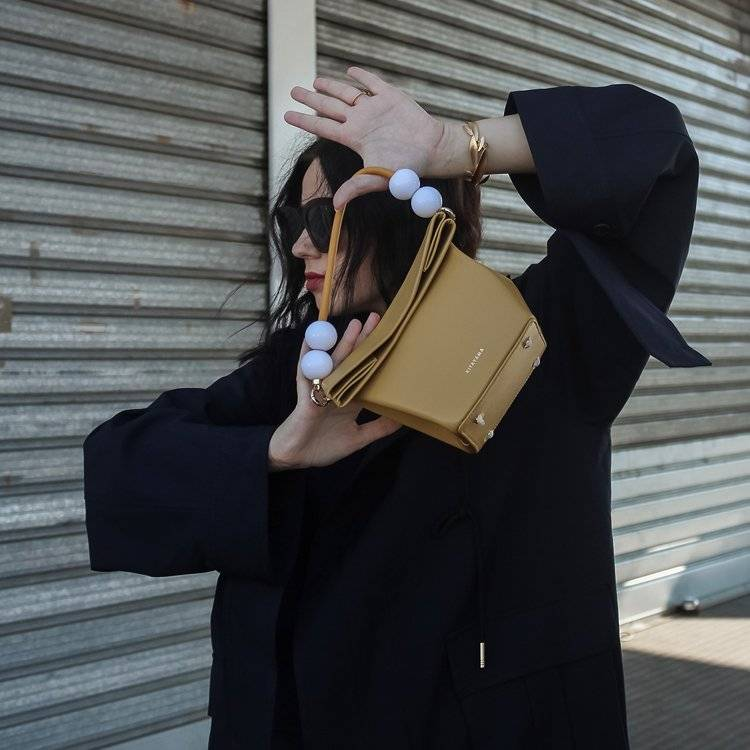 a woman with black dress is holding a bag