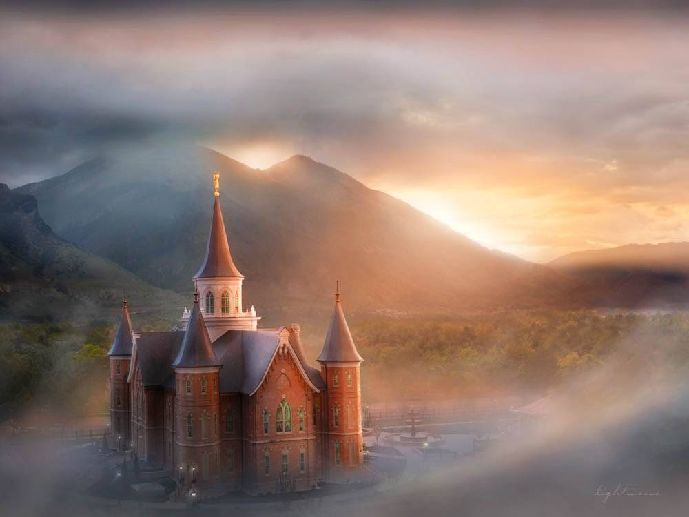 Provo City Center LDS Temple stands amid sunrays and fog.