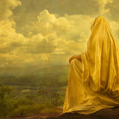 Jesus in a yellow robe sitting on a hill and looking out at the landscape.
