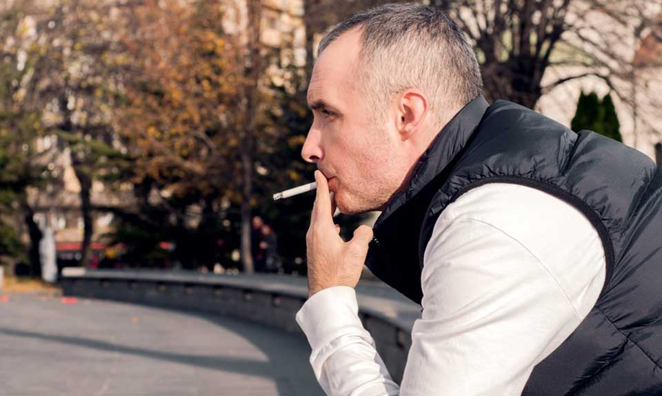 man with hair loss smoking a cigarette