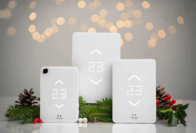 three Mysa Smart Thermostat products surrounded by holiday greenery and pinecones