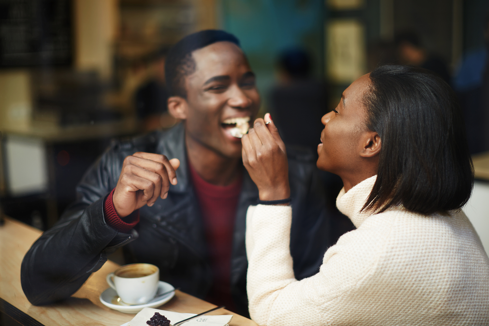 Image of a black young couple at a coffee shop, the woman is giving a spoonfull of food to her friend and he is smiling.