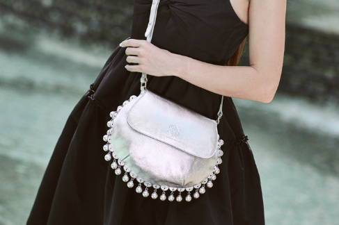 A crossbody view of the CHARMAINE sharp silver shoulder bag with hanging pearl charms